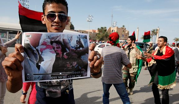 A man holds a photo said to be of the body of Col. Moammar Gadhafi after announcement of the former leader's death in Tripoli, Libya, on Oct. 20, 2011. (Associated Press)