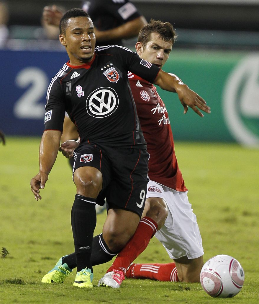 D.C. United's Charlie Davies (9) moves the ball as Portland Timbers' Eric Brunner defends during the first half of an MLS soccer game,Wednesday, Oct. 19, 2011, in Washington. The game ended in a 1-1 tie. (AP Photo/Luis M. Alvarez)
