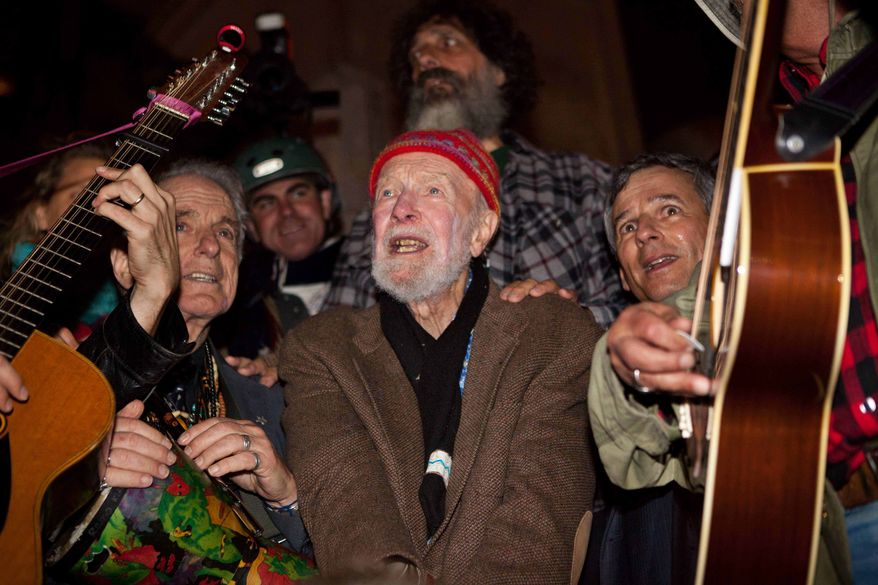 Activist musician Pete Seeger, 92, center, sings before a crowd of nearly a thousand demonstrators sympathetic to the Occupy Wall Street protests at a brief acoustic concert in Columbus Circle, Saturday, Oct. 22, 2011, in New York. (AP Photo/John Minchillo)