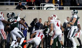 Michigan State receiver Keith Nichol (right) grabbed this tipped Hail Mary from quarterback Kirk Cousins and plunged into the end zone Saturday to give the Spartans a 37-31 upset of Wisconsin. (Associated Press)