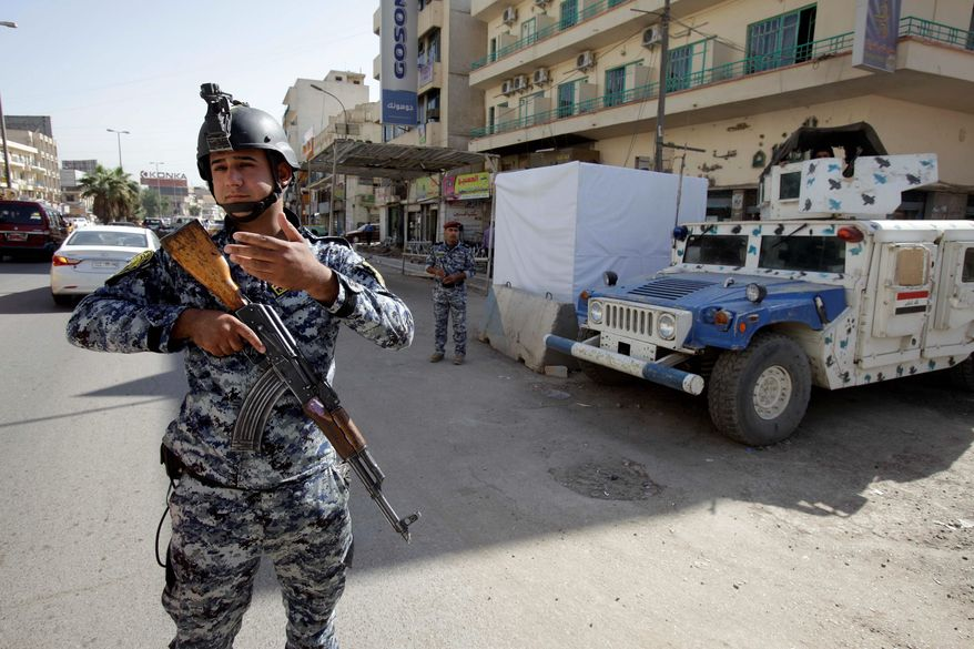 """An Iraqi police officer mans a checkpoint in central Baghdad. A U.S. State Department program to train Iraqi police lacks focus, could become a """"bottomless pit"""" of American money, and is not even appreciated by the Iraqi government, a U.S. government watchdog warns in a report. (Associated Press)"""