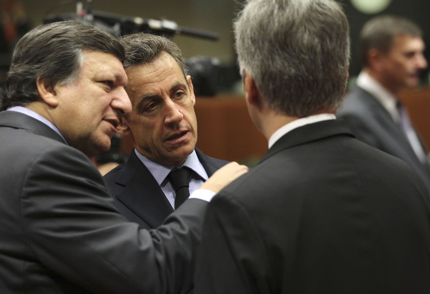 French President Nicolas Sarkozy (center) and European Commission President Jose Manuel Barroso (left) speak with Austrian Chancellor Werner Faymann during a round-table meeting at a European Union summit in Brussels on Sunday, Oct. 23, 2011. (AP Photo/Yves Logghe)