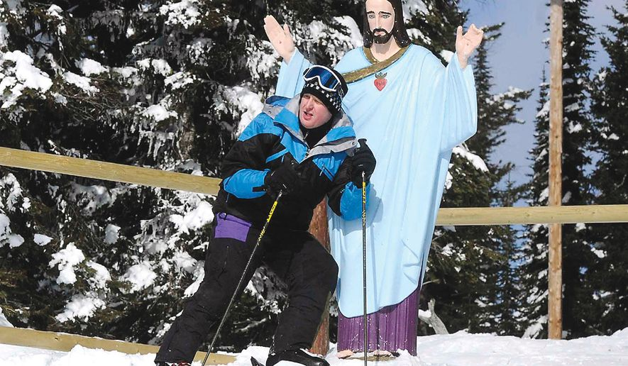 Lyle Burke of the Canadian province of Alberta poses with the statue of Jesus Christ near the top of Chair 2 at the Whitefish Mountain Resort in Montana in February. The statue, erected in 1953 to honor World War II veterans, may have to be removed after the U.S. Forest Service recently denied a special-use permit allowing the stone statue. (AP Photo/The Missoulian, Linda Thompson)