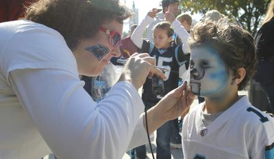 Jennifer Szakaly, left, paints a Panthers face onto Haiden Anderson, 5, of Charlotte, N.C., right, before an NFL football game between the Carolina Panthers and the Washington Redskins in Charlotte, N.C., Sunday, Oct. 23, 2011. (AP Photo/Bob Leverone)