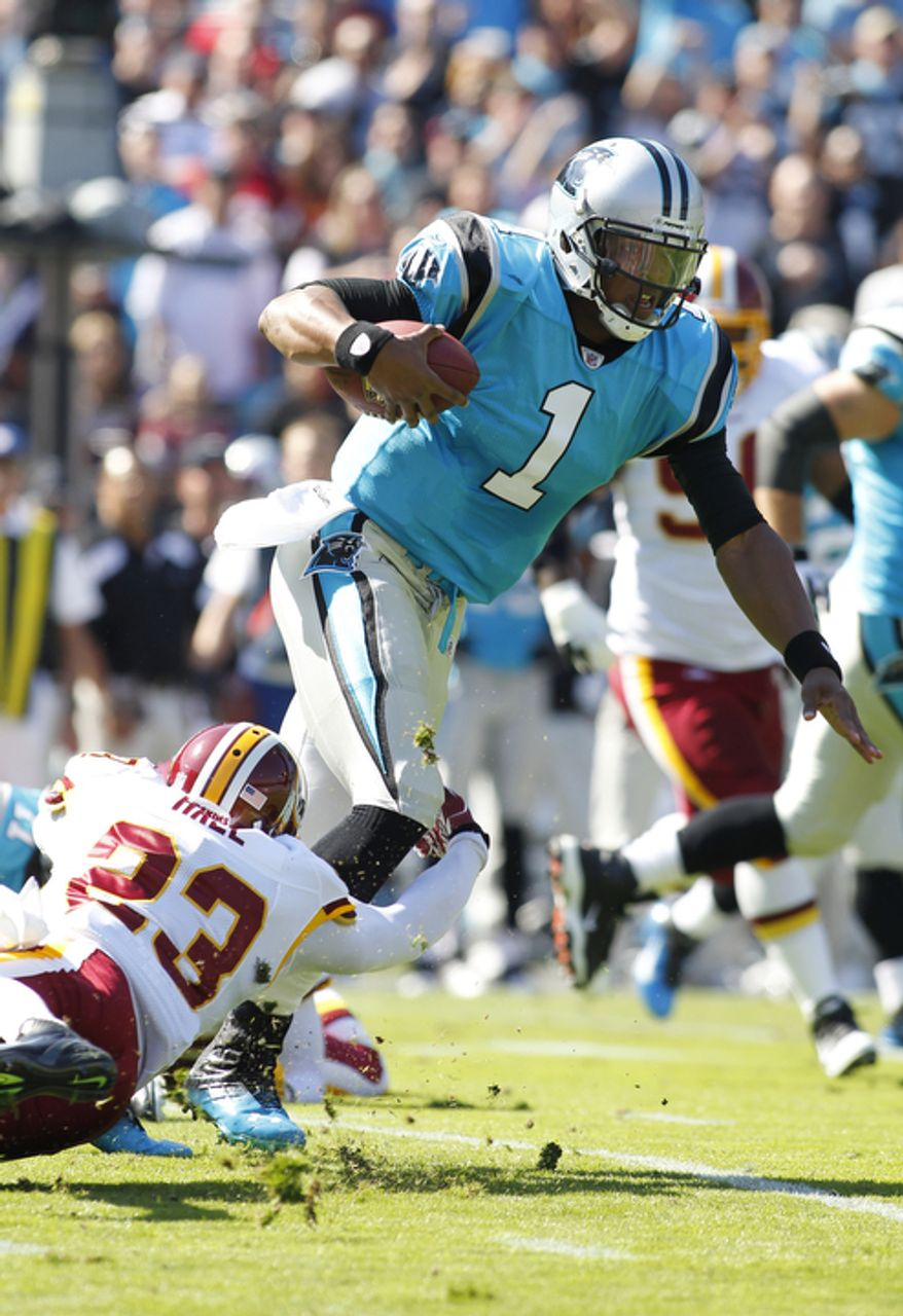 Carolina Panthers' Cam Newton (1) runs through the tackle of Washington Redskins' DeAngelo Hall (23) during the first quarter of an NFL football game in Charlotte, N.C., Sunday, Oct. 23, 2011. (AP Photo/Bob Leverone)