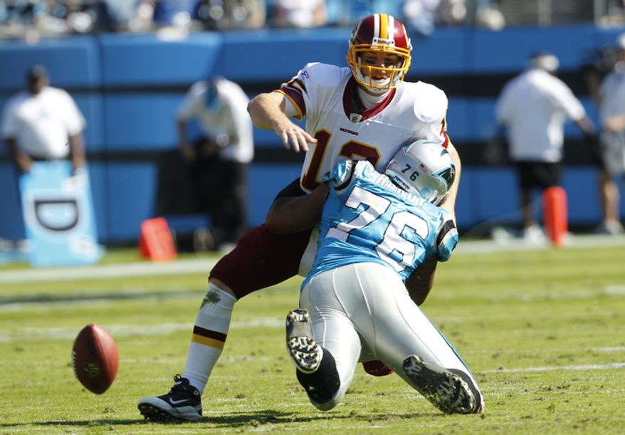 Washington Redskins' John Beck (12) loses the ball as he is hit by Carolina Panthers' Greg Hardy (76) during the second quarter of an NFL football game in Charlotte, N.C., Sunday, Oct. 23, 2011.  The play was ruled an incomplete pass. (AP Photo/Chuck Burton)