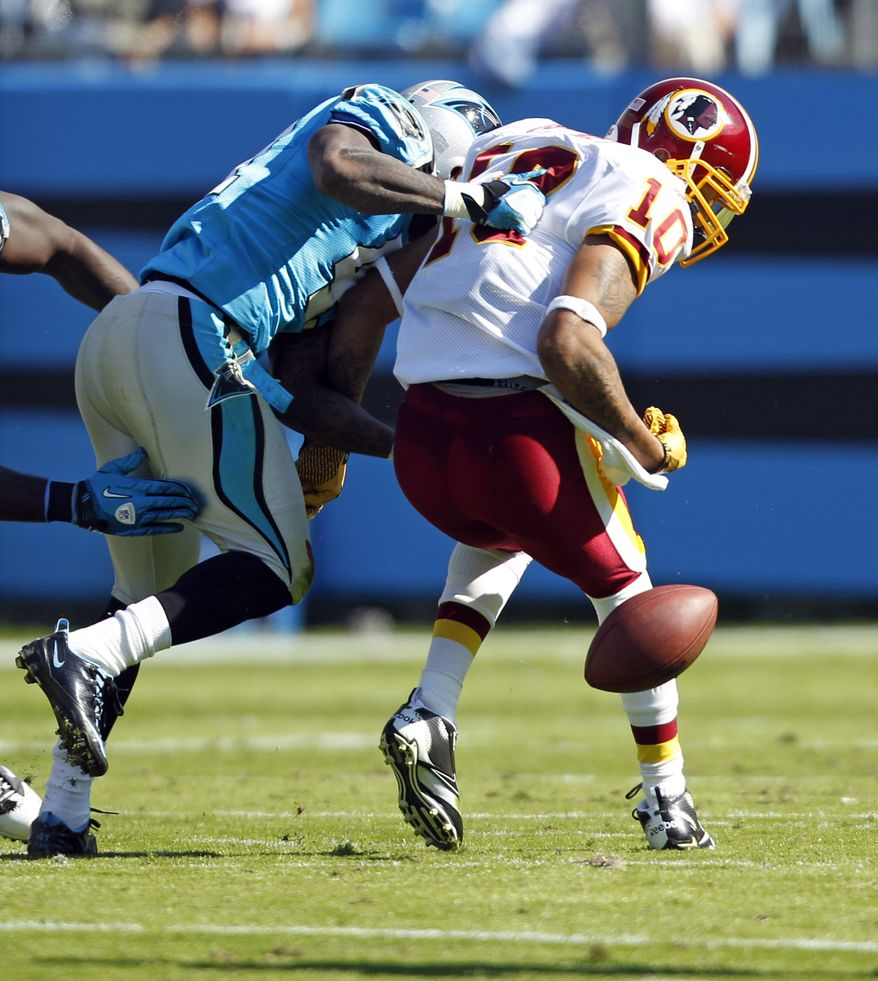 Washington Redskins' Jabar Gaffney fumbles the ball as he is hit by Carolina Panthers' Captain Munnerlyn during the second quarter in Charlotte, N.C., Sunday, Oct. 23, 2011. (AP Photo/Chuck Burton)