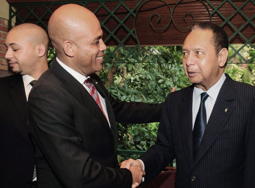 """Haiti's President Michel Martelly (center) shakes hands with former dictator Jean-Claude Duvalier in Port-au-Prince on Oct. 12 with Mr. Duvalier's son, Francois Nicolas """"Nico"""" Duvalier, present (left). Mr. Martelly has not sought prosecution of the former dictator, who has been accused of looting the treasury and torturing and killing political opponents. (Associated Press)"""