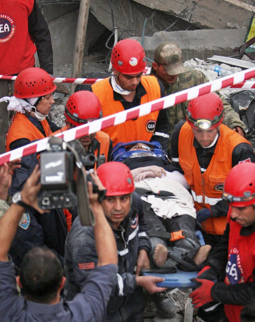 Rescue workers evacuate a victim after pulling her from earthquake rubble in the town of Ercis in Van province, Turkey. The 7.2-magnitude quake Sunday killed an estimated 300 people in eastern Turkey. (Associated Press)