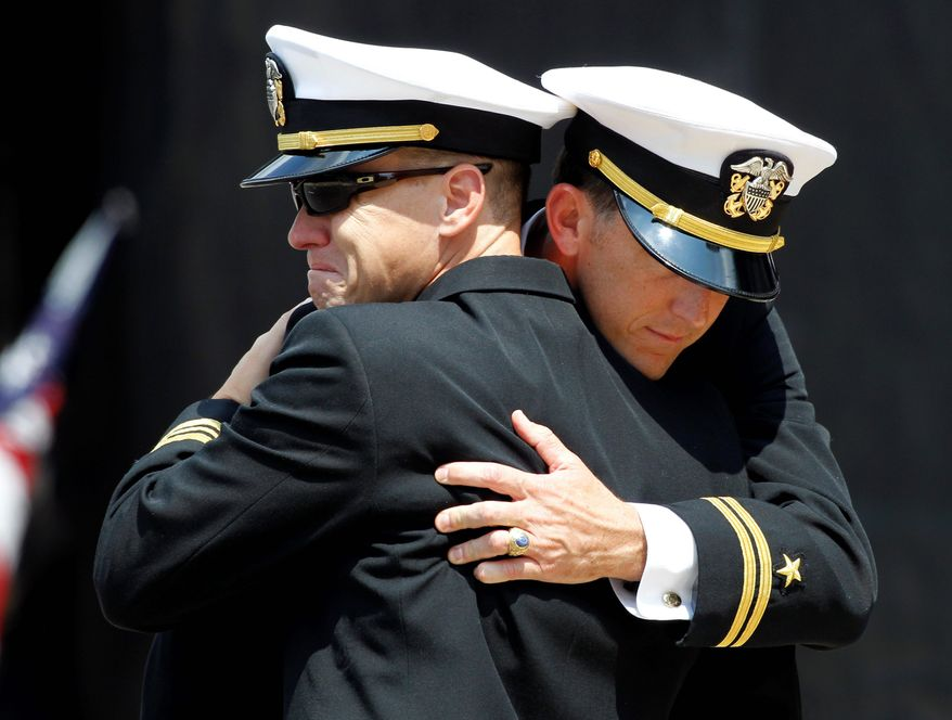Naval officers console each other at funeral services for Petty Officer 1st Class Michael Joseph Strange, who was among the 17 SEALs killed on Aug. 6. As friends and families mourned, Army Brig. Gen. Jeffrey Colt and a team of specialists were conducting a full-blown investigation. (Associated Press)