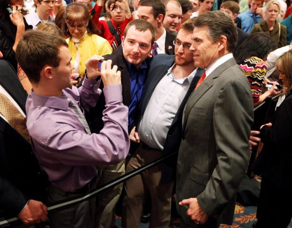 Presidential candidate Texas Gov. Rick Perry (right) poses with supporters after speaking at GOP forum Oct. 12 in Indianapolis. Barack Obama won Indiana in 2008, so to restore the state's reputation for producing conservative wins, the Republican National Committee plans to send staffers and funding to Indiana in the spring, says Rick Wiley, RNC political director. (Associated Press)