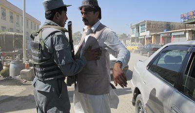 ** FILE ** An Afghan policeman body-checks a man in Khost, Afghanistan, on Sunday, Oct. 2, 2011, after security measures were tightened following the capture of Haji Mali Khan, a senior Haqqani leader inside Afghanistan. (AP Photo/Nishanuddin Khan)