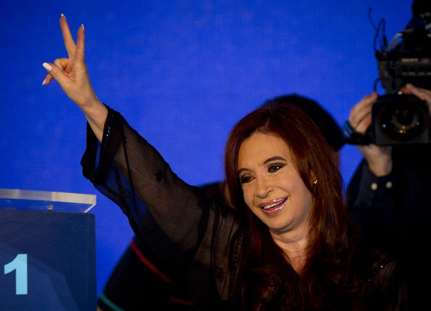 ** FILE ** Argentine President Cristina Fernandez flashes a victory sign while celebrating her re-election with supporters in Buenos Aires on Sunday, Oct. 23, 2011. (AP Photo/Victor R. Caivano)