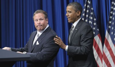 Stephen Cloobeck (left) of the Board of Directors for Corporation for Travel Promotion looks back at President Obama as he is introduced at a fundraiser at the Bellagio Hotel in Las Vegas on Oct. 24, 2011. (Associated Press)