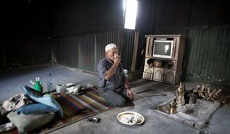 An Israeli Bedouin man drinks coffee in his village near the southern Israeli city of Beersheba, the Negev's main city. The nomadic people are clustered in impoverished towns and villages, many devoid of basic services. (Associated Press)