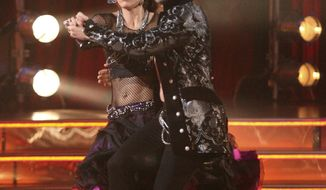 "In this Oct. 17, 2011, photo, soccer player Hope Solo, left, and her partner Maksim Chmerkovskiy perform in the celebrity dance competition series ""Dancing with the Stars,"" in Los Angeles. (AP Photo/ABC, Adam Taylor)"