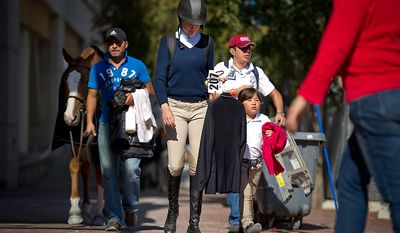Rider and trainer Katie Taylor (center) of Los Angeles walks back to their stables with her 7-year-old pupil Augusta Iwasaki (right) at the annual Washington International Horse Show on Oct. 25, 2011, in D.C. The event runs Oct. 25-30 at the Verizon Center and features top riders and horses from the U.S. and abroad. (Andrew Harnik/The Washington Times)