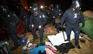 """Police search tents in Frank Ogawa Plaza in Oakland, Calif., on Tuesday, Oct. 25, 2011, as they disperse """"Occupy Oakland"""" protesters. (AP Photo/Bay Area News Group, Jane Tyska)"""