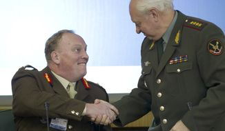 Gen. Vladimir Yakovlev (right), head of the general staff of the Russian armed forces academy, and British Maj. Gen. Simon Porter shake hands as they open the Russia-NATO seminar in Moscow on Tuesday, Oct. 25, 2011. (AP Photo/Ivan Sekretarev)