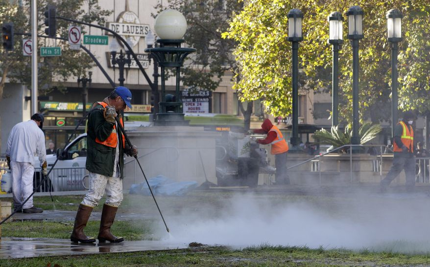 Public works personnel in Oakland, Calif., use steam cleaners as they continue to sanitize Frank H. Ogawa Plaza on Wednesday. Protesters have been trying to stay in the plaza since being evicted Tuesday morning. (Associated Press)