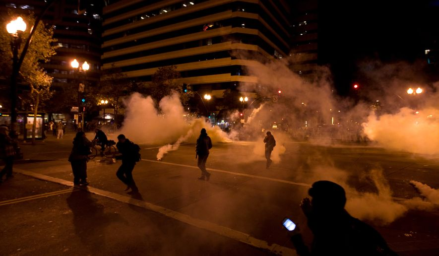 """""""Occupy Wall Street"""" protesters run from tear gas deployed by police at 14th Street and Broadway in Oakland, Calif., on Tuesday, Oct. 25, 2011. (AP Photo/Darryl Bush)"""