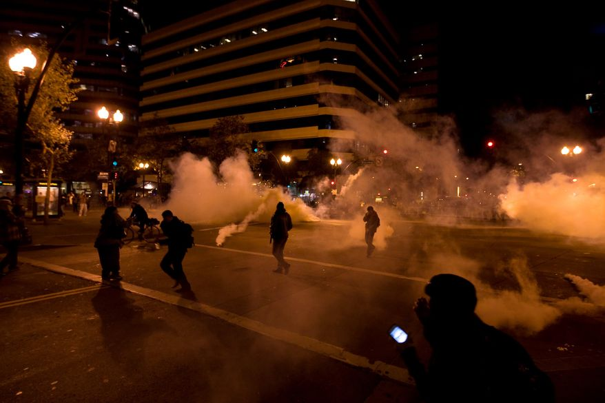 """Occupy Wall Street"" protesters run from tear gas deployed by police at 14th Street and Broadway in Oakland, Calif., on Tuesday, Oct. 25, 2011. (AP Photo/Darryl Bush)"