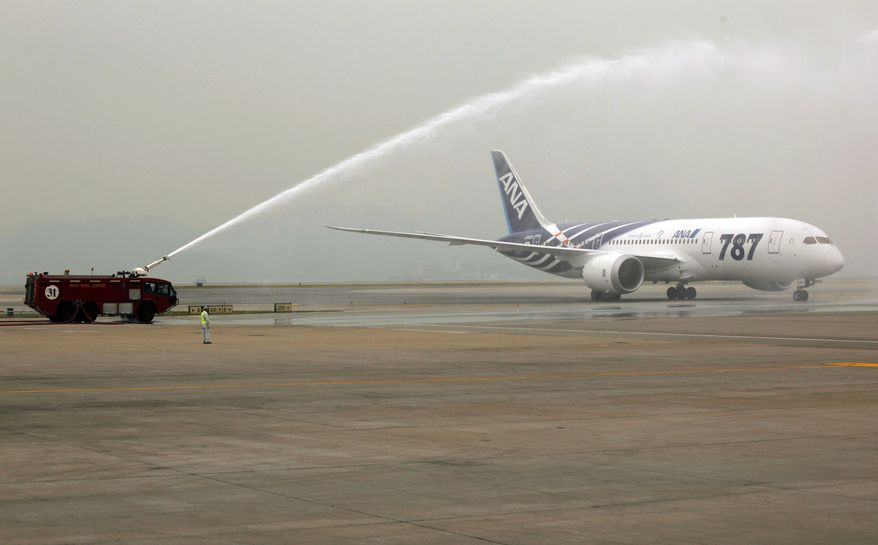 """A traditional spray of water marks the arrival of an All Nippon Airways Boeing 787 """"Dreamliner"""" to celebrate the model's inaugural commercial flight from Tokyo's Narita International Airport to Hong Kong International Airport on Wednesday, Oct. 26, 2011. (AP Photo/Vincent Yu)"""