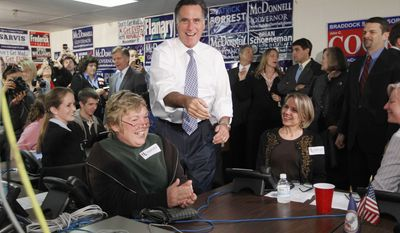 Former Massachusetts Gov. Mitt Romney, a candidate for the Republican presidential nomination, greets volunteers at a call center at the Fairfax County Republican Committee headquarters in Fairfax, Va., on Wednesday, Oct. 26, 2011. (AP Photo/Pablo Martinez Monsivais)