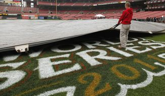A worker removes a tarp from the infield at Busch Stadium in St. Louis on Wednesday, Oct. 26, 2011, after officials announced that Game 6 of the World Series had been postponed because of rain. (AP Photo/Jeff Roberson)