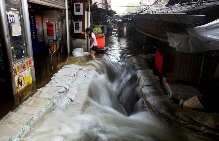 A woman struggles to walk as floodwaters gush through a marketplace Thursday in a riverside neighborhood near Bangkok's Grand Palace, built in the 18th century. Clamoring aboard bamboo rafts and army trucks, residents living on the heavily inundated outskirts of Bangkok fled waterlogged homes as floodwaters moved closer to the heart of the Thai capital. (Associated Press)