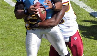 Carolina Panthers' Cam Newton is sacked by Washington Redskins' Brian Orakpo during the second quarter in Charlotte, N.C., Sunday, Oct. 23, 2011. (AP Photo/Mike McCarn)