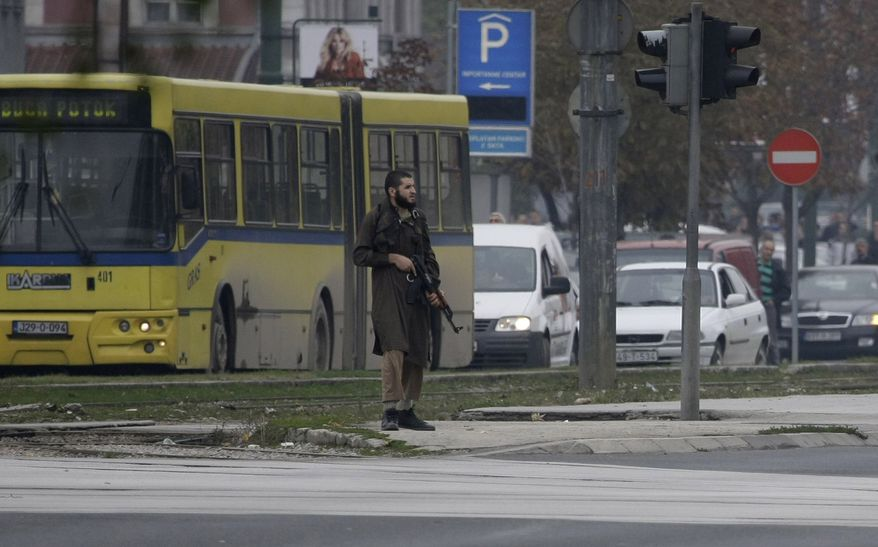 An unidentified gunman stands in the center of the street in Sarajevo, Bosnia, on Oct. 28, 2011, at a street in front of the U.S. embassy. The man shot several rounds at pedestrians in downtown Sarajevo on Friday and injured at least one officer before police special forces took him down. For at least 30 minutes, the man stood at a street in front of the U.S. embassy in Sarajevo and shot around from an automatic rifle. (Associated Press)