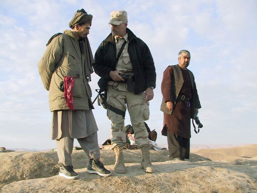 REMINDER: Now-retired Lt. Col. Max Bowers, Special Forces ground commander, advises Northern Alliance warlords in Afghanistan in November 2001. He was carrying with him a piece of the World Trade Center at the time. (Army Special Operations Command)
