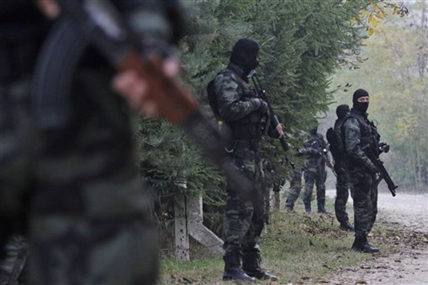 Bosnian special police units get ready to check the personal ID of the residents on the road towards Bosnian village of Gornja Maoca, 200 kms north from Sarajevo, on Saturday,Oct. 29, 2011. Special police units raided homes Saturday in a Bosnian village linked to the gunman who fired an automatic weapon at the U.S. Embassy in Sarajevo in what authorities called a terrorist attack. The raids came as 17 suspected associates of the shooter, all said to be members of the ultraconservative Wahhabi Muslim sect, were briefly detained in Serbia. (AP Photo/Amel Emric)