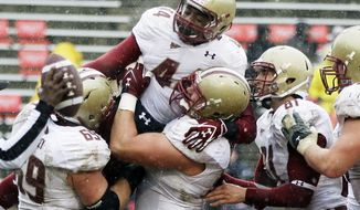 Boston College running back Andre Williams, top center, celebrates with his teammates after scoring a touchdown in the first half against Maryland in College Park, Md., Saturday, Oct. 29, 2011. (AP Photo/Patrick Semansky)