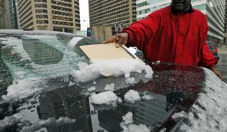 Les Lewis uses a clipboard to scrape the snow off of the back of his car window Saturday, Oct. 29, 2011, in Philadelphia, Pa. A classic nor'easter was chugging along up the East Coast and expected to dump anywhere from a dusting of snow to about 10 inches throughout the region starting Saturday, a decidedly unseasonal date for a type of storm more associated with midwinter. (AP Photo/Alex Brandon)