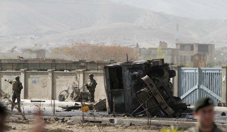 U.S. soldiers (left) guard the site of a suicide car bombing of a NATO convoy on the outskirts of Kabul, Afghanistan, on Saturday, Oct. 29, 2011. (AP Photo/Ahmad Jamshid)