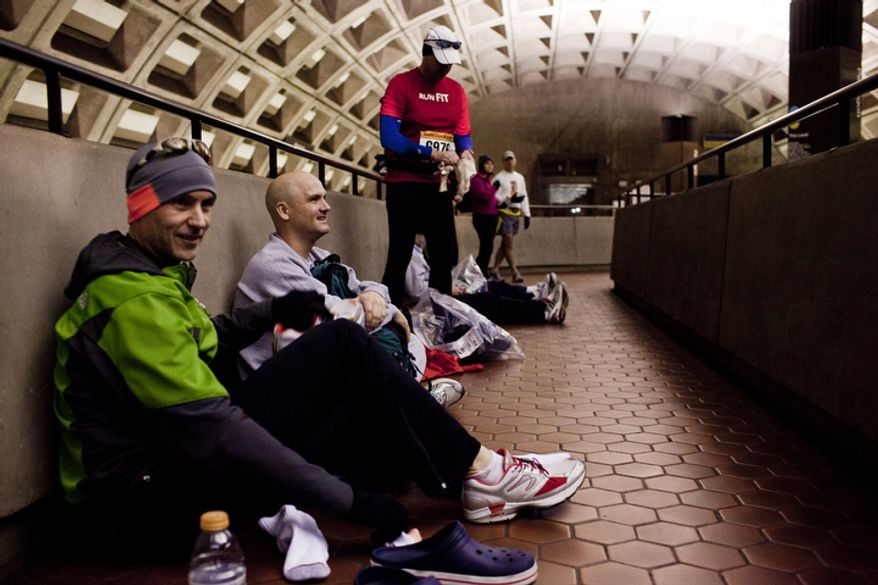 """Todd Bryant, of Springfield, Va., from left, Steve Cribby, of Bowie, Md., and Stanley Cowan, of Washington, D.C., wait inside the Pentagon metro station to """"stay warm as long as I can,"""" said Bryant, before running in the 36th Marine Corps Marathon in Arlington, Va. on Oct. 30, 2011.(T.J. Kirkpatrick/ The Washington Times)"""