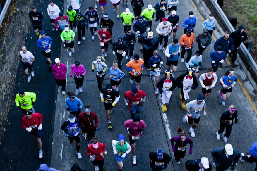 Runners, including Sean Kelly and Justin Laddusaw, both of Annapolis, Md., from left wearing penguin costumes, start the 36th Marine Corps Marathon in Arlington, Va. on Oct. 30, 2011.(T.J. Kirkpatrick/ The Washington Times)