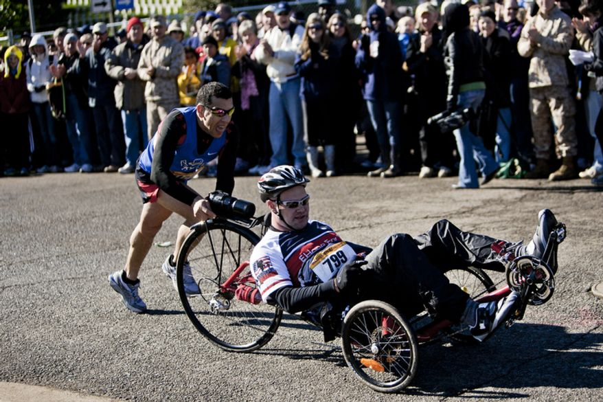 Johnathon Rose, of Houston, Texas, gets a push up the hill from Staff Sgt. Jose Garza, left, stationed at Elmendorf Air Force Base in Texas, as they approach the finish of the 36th Marine Corps Marathon in Arlington, Va. on Oct. 30, 2011.