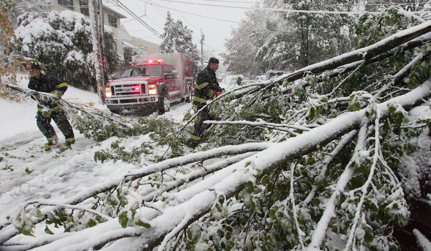 Frank Forgione (center) of the West Harrison (N.Y.) Fire Department removes branches from a fallen tree to free a damaged vehicle on Saturday, Oct. 29, 2011. (AP Photo/The Journal News, Xavier Mascarenas)