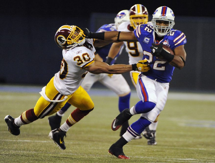 Buffalo Bills' Fred Jackson runs under pressure from Washington Redskins' LaRon Landry during the first half at Rogers Centre in Toronto, Sunday, Oct. 30, 2011. (AP Photo/Gary Wiepert)