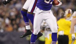 Buffalo Bills' Drayton Florence and teammate George Wilson celebrate Wilson's interception of a pass from Washington Redskins' John Beck during the second half in Toronto on Sunday, Oct. 30, 2011. (AP Photo/Derek Gee)