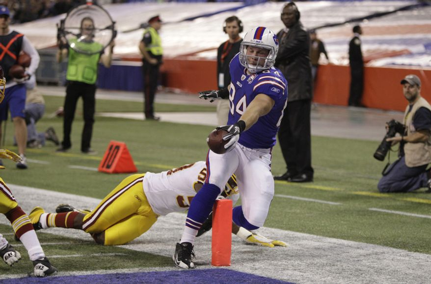 Buffalo Bills' Scott Chandler (84) scores a touchdown under pressure from Washington Redskins' London Fletcher (59) during the first quarter of an NFL football game at the Rogers Centre in Toronto, Sunday, Oct. 30, 2011. (AP Photo/David Duprey)