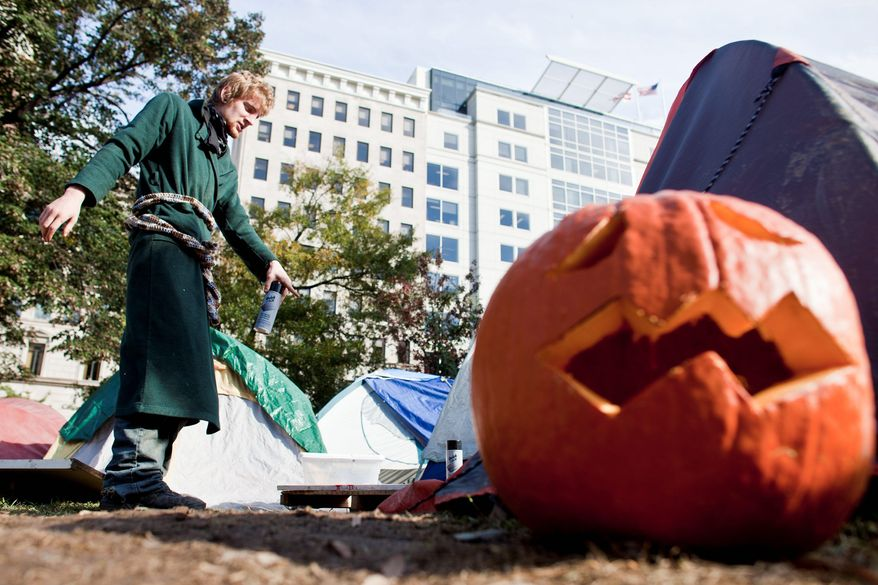 An Occupy DC protester, who did not want to be identified, paints a sign Monday among the tents in McPherson Square. Signs of Halloween, too, were evident at the encampment, but theatrics were kept low key. (T.J. Kirkpatrick/The Washington Times)