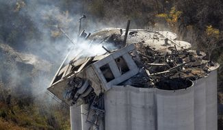 Smoke rises from the damaged headhouse area of the Bartlett Grain Co. elevator in Atchison, Kan., on Sunday, Oct. 30, 2011. (AP Photo/The Kansas City Star, Keith Myers)