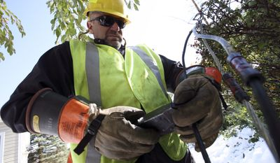 Bob Wyman, an underground lineman with Public Service Electric and Gas Co., makes a temporary repair to restore electricity to a home in Verona, New Jersey, on Sunday, Oct. 30, 2011. (AP Photo/David Gard)