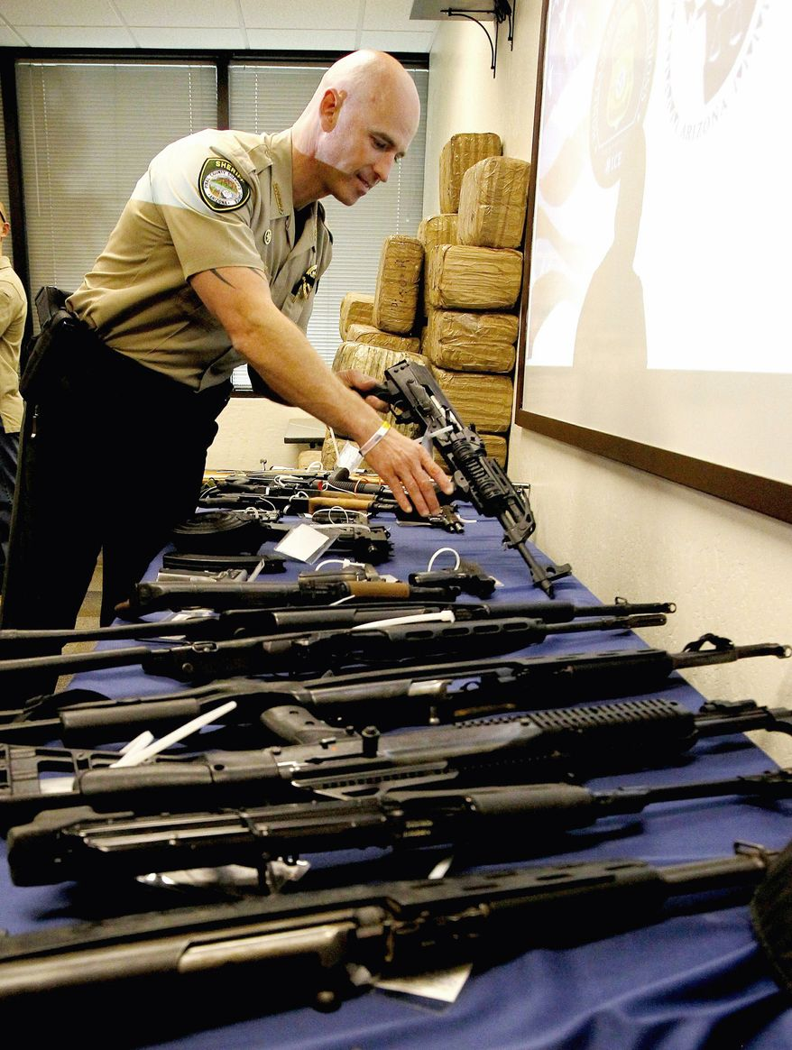 Pinal County Sheriff Paul Babeu checks a seized weapon after a news conference Monday during which multijurisdictional law enforcement agencies announced a bust of a major drug smuggling ring in Arizona. (Associated Press)