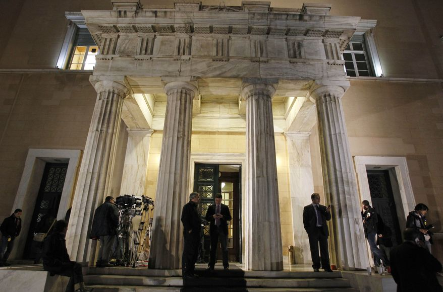 Media gather outside the Greek parliament during a cabinet meeting in Athens on Nov. 1, 2011. Lawmakers in Greece's ruling Socialist party revolted over their prime minister's surprise decision to hold a referendum on a European debt deal, threatening the very survival of his embattled government. (Associated Press)