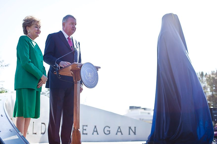 Former Transportation Secretary Elizabeth Dole (left) and Charles Snelling, chairman of the board of the Metropolitan Washington Airports Authority, speak at a dedication ceremony for a bronze statue of Ronald Reagan at Reagan National Airport in Arlington, Va., on Nov. 1, 2011. The statue was unveiled as part of a dedication ceremony on the centennial of the former president's birth. (T.J. Kirkpatrick/The Washington Times)
